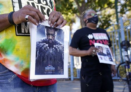 """Portrait of the late actor Chadwick Boseman as the character T'Challa in the 2018 film """"Black Panther"""" is held by a participant in a news conference celebrating his life, Saturday, Aug. 29. 2020, in Los Angeles. Boseman died Friday at 43 after a four-year fight with colon cancer"""