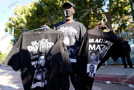 """Mack Freedom of Los Angeles holds """"Black Panther"""" and """"Black Lives Matter"""" t-shirts during a news conference to celebrate the late actor Chadwick Boseman, the star of 2018 film """"Black Panther,"""" Saturday, Aug. 29. 2020, in Los Angeles. Boseman died Friday at 43 after a four-year fight with colon cancer"""