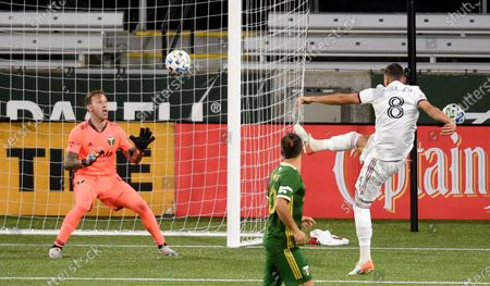 Real Salt Lake midfielder Damir Kreilach, right, score a goal past Portland Timbers goalkeeper Steve Clark, left, during the second half of an MLS soccer match in Portland, Ore., . The match ended in a 4-4 draw