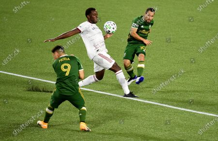 Stock Image of Portland Timbers midfielder Sebastian Blanco, right, scores a goal past Real Salt Lake defender Nedum Onuoha, center, as Timbers forward Felipe Mora, left, ducks out of the way during the second half of an MLS soccer match in Portland, Ore., . The match ended in a 4-4 draw