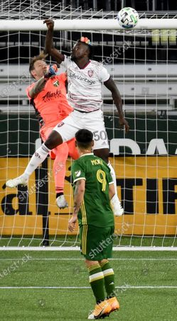 Real Salt Lake forward Sam Johnson, right, goes up for the ball next to Portland Timbers goalkeeper Steve Clark, left, during the second half of an MLS soccer match in Portland, Ore., . The match ended in a 4-4 draw. AP Photo/Steve Dykes