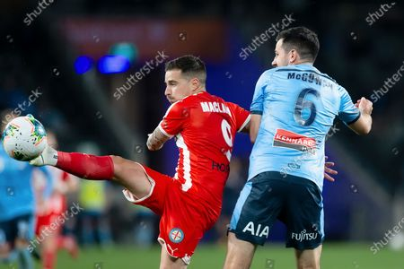 Stock Image of Melbourne City forward Jamie Maclaren (9) passes the ball under pressure from Sydney FC defender Ryan McGowan (6)