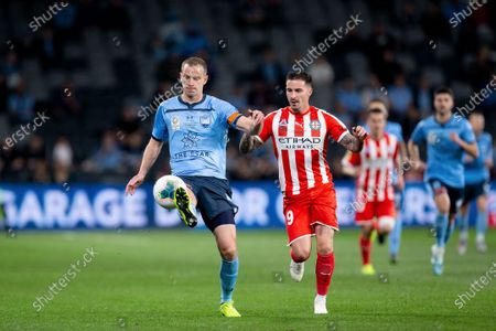 Sydney FC defender Alex Wilkinson (4) clears the ball under pressure from Melbourne City forward Jamie Maclaren (9)