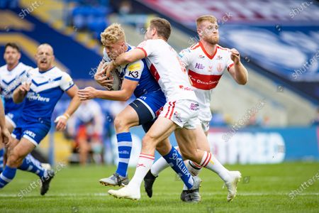 Aaron Smith of St Helens is tackled by Daniel Murray and Matt Parcell of Hull KR.