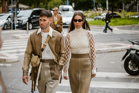 Jean-Sebastien Rocques wears a cream-color shirt, a sand-color jacket, a light brown Fendi crossbody bag, light grey pants with brown pockets. Alice Barbier wears a cream-color hi-neck mesh top, a sand-color leather mesh skirt,seen outside Fendi show during Milan Fashion Week Womenswear Spring Summer 2020