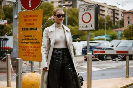 Pernille Teisbaek wears sunglasses, earrings, a necklace, a cream-color hi-neck top, a cream-color leather coat, black leather crocodile pattern pants, a black Fendi bag, seen outside Fendi show during Milan Fashion Week Womenswear Spring Summer 2020