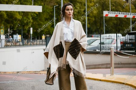 Stock Image of Adrianne Ho wears a white shirt, a cream-color fringed Fendi poncho, a camel bag, light brown wide-legs pants, seen outside Fendi show during Milan Fashion Week Womenswear Spring Summer 2020