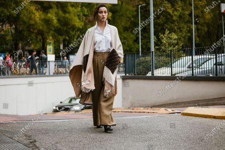 Stock Picture of Adrianne Ho wears a white shirt, a cream-color fringed Fendi poncho, a camel bag, light brown wide-legs pants, black pointy shoes, seen outside Fendi show during Milan Fashion Week Womenswear Spring Summer 2020