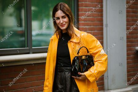 Gala Gonzalez is seen wearing black skirt, yellow coat, black Fendi bag, shirt, seen outside Fendi show during Milan Fashion Week Womenswear Spring Summer 2020