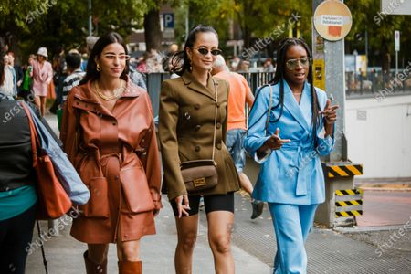 Bettina Looney wearing rusty brown coat, boots. Anna Rosa Vitiello wearing cycle pants, olive double breasted jacket, Fendi bag. Chrissy Rutherford wearing blue jacket and pants, seen outside Fendi show during Milan Fashion Week Womenswear Spring Summer 2020