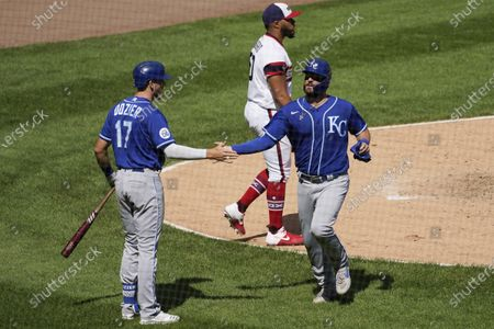 Kansas City Royals' Cam Gallagher, right, celebrates with Hunter Dozier after scoring on a one-run single by Whit Merrifield as Chicago White Sox relief pitcher Jimmy Cordero, top, looks to the field during the sixth inning of a baseball game in Chicago