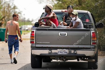 Linda Smoot, right, Rakisha Murray, center, and Bernie Murray who evacuated from Hurricane Laura in a pickup truck with eight others, react to the scenes of devastation as they return to see their homes for the first time, in Lake Charles, La., in the aftermath of the hurricane