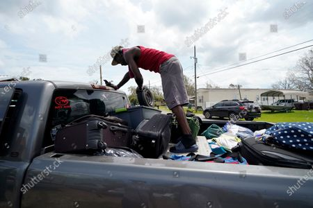 Bernie Murray rearranges luggage in Lake Charles, La., as he returns with eight family members in one truck, after evacuating from Hurricane Laura