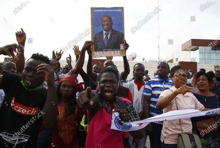 Supporters of former President Laurent Gbagbo, barred from participating in the October presidential election, carry his picture as they gather to defy the ruling by waiting for the arrival of the representative of their candidate to submit application for October election at the Independent Electoral Commission office in Abidjan, Ivory Coast, 31 August 2020. The supporters have said they will file his candidacy in his name for the country's presidential elections scheduled for 31 October 2020. Candidates have until midnight on 31 August to submit their bids for the presidential race. Gbagbo remains in Belgium where he awaits a passport to return home after being cleared of crimes against humanity by the International Criminal Court at the Hague in 2019.