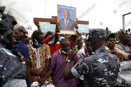 Supporters of former President Laurent Gbagbo, barred from participating in the October presidential election gather as they plan to defy the ruling by waiting for the arrival of the representative of their candidate to submit application for October election at the Independent Electoral Commission office in Abidjan, Ivory Coast, 31 August 2020. The supporters have said they will file his candidacy in his name for the country's presidential elections scheduled for 31 October 2020. Candidates have until midnight on 31 August to submit their bids for the presidential race. Gbagbo remains in Belgium where he awaits a passport to return home after being cleared of crimes against humanity by the International Criminal Court at the Hague in 2019.