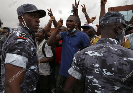 Policemen stand guard as supporters of former President Laurent Gbagbo, barred from participating in the October presidential election, react as they gather to defy the ruling by waiting for the arrival of the representative of their candidate to submit application for October election at the Independent Electoral Commission office in Abidjan, Ivory Coast, 31 August 2020. The supporters have said they will file his candidacy in his name for the country's presidential elections scheduled for 31 October 2020. Candidates have until midnight on 31 August to submit their bids for the presidential race. Gbagbo remains in Belgium where he awaits a passport to return home after being cleared of crimes against humanity by the International Criminal Court at the Hague in 2019.