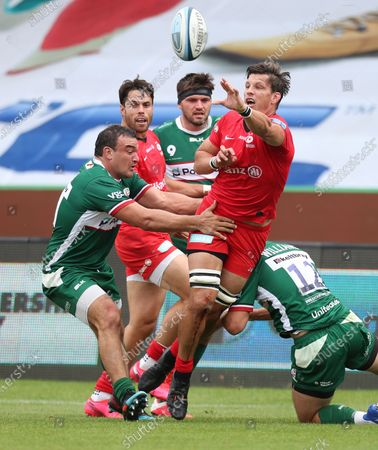 Michael Rhodes of Saracens offloads the ball tackled by Agustin Creevy (left) and Matt Williams of London Irish
