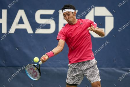 Yasutaka Uchiyama, of Japan, returns a shot to Pablo Carreno Busta, of Spain, during the first round of the US Open tennis championships, in New York