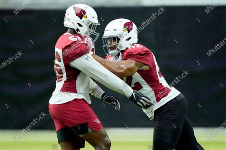 Arizona Cardinals' Reggie Walker, left, and Devon Kennard run drills during an NFL football training camp, in Glendale, Ariz