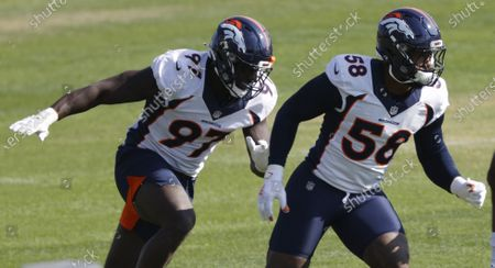 Denver Broncos linebackers Von Miller, right, and Jeremiah Attaochu take part in drills during an NFL football practice, in Englewood, Colo