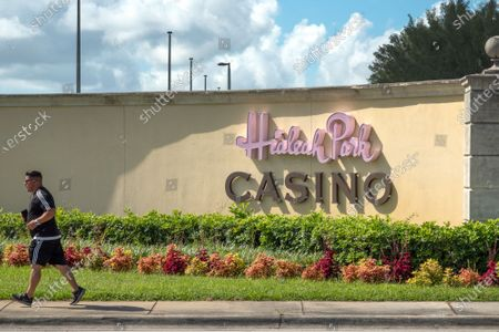 A man runs in front of the entrance of the Hialeah Park Casino in Hialeah, Florida, USA, 31 August. Miami-Dade Mayor Carlos Gimenez allowed casinos to reopen on 31 August after an eight-week closure, lifting restrictions on the entertainment hubs on the same day he lets restaurants resume indoor dining.