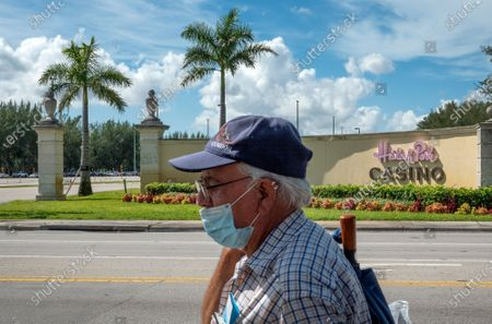 A man walks in front of the entrance of the Hialeah Park Casino in Hialeah, Florida, USA, 31 August. Miami-Dade Mayor Carlos Gimenez allowed casinos to reopen on 31 August after an eight-week closure, lifting restrictions on the entertainment hubs on the same day he lets restaurants resume indoor dining.