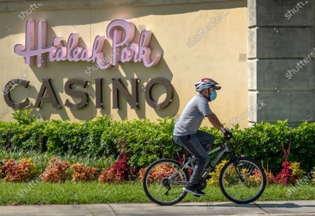 A man rides a bike in front of the entrance of the Hialeah Park Casino in Hialeah, Florida, USA, 31 August. Miami-Dade Mayor Carlos Gimenez allowed casinos to reopen on 31 August after an eight-week closure, lifting restrictions on the entertainment hubs on the same day he lets restaurants resume indoor dining.
