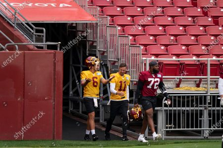 Washington quarterback Steven Montez (6), quarterback Alex Smith (11), and defensive end James Smith-Williams (72) walk on the field for an NFL football practice at FedEx Field, in Washington