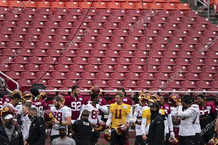 The Washington team gathers, including quarterback Alex Smith (11), for an NFL football practice at FedEx Field, in Washington