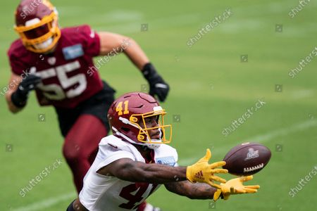 Washington running back J.D. McKissic (41) catches a pass in front of linebacker Cole Holcomb (55) during an NFL football practice at FedEx Field, in Washington