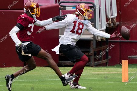 Washington defensive back Simeon Thomas defends against wide receiver Trey Quinn (18) during an NFL football practice at FedEx Field, in Washington