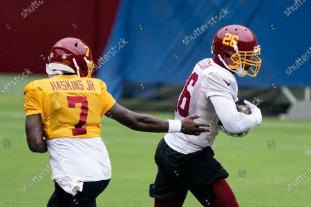 Washington quarterback Dwayne Haskins Jr. (7) hands the ball off to running back Adrian Peterson (26) during an NFL football practice at FedEx Field, in Washington