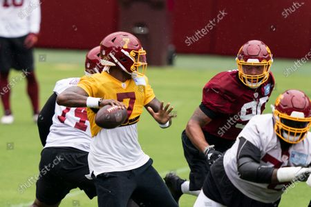 Washington quarterback Dwayne Haskins Jr. (7) looks to pass with defensive end Montez Sweat (90) nearby during an NFL football practice at FedEx Field, in Washington
