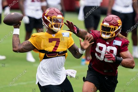 Washington quarterback Dwayne Haskins Jr. (7) passes under pressure from defensive end Chase Young (99) during an NFL football practice at FedEx Field, in Washington