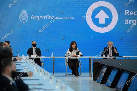 Argentina's Vice-President Cristina Fernandez, center, and Economy minister Martin Guzman, left, listen to President Alberto Fernandez speak during a ceremony announcing the results of the restructuring of its overseas debt, at the Casa Rosada government house in Buenos Aires, . The Argentine government formalized an agreement with private creditors to restructure its debt for 65 billion dollars after five months of tense negotiations