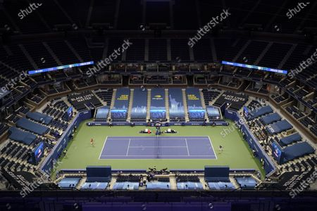 Stands at Arthur Ashe Stadium sit nearly empty as Novak Djokovic, of Serbia, right, returns to Damir Dzumhur, of Bosnia and Herzegovina, during the first round of the US Open tennis championships, in New York