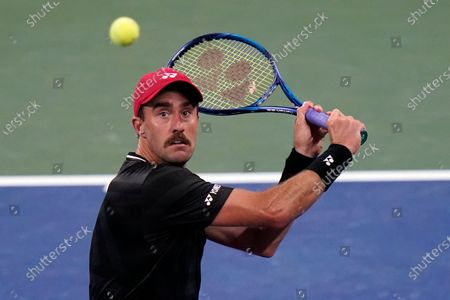 Stock Image of Steve Johnson, of the United States, returns to John Isner, of the United States, during the first round of the US Open tennis championships, in New York
