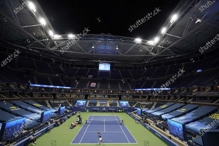 The stands of Arthur Ashe Stadium sit nearly empty as Novak Djokovic, of Serbia, below, serves to Damir Dzumhur, of Bosnia and Herzegovina, during the first round of the US Open tennis championships, in New York