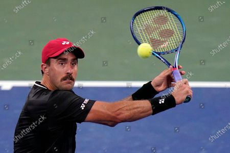 Stock Photo of Steve Johnson, of the United States, returns to John Isner, of the United States, during the first round of the US Open tennis championships, in New York