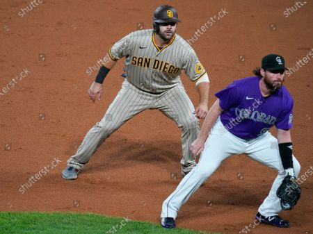 San Diego Padres' Mitch Moreland, back, appearing in his first game since being acquired in a trade with the Boston Red Sox, takes a lead off first base as Colorado Rockies first baseman Daniel Murphy watches the batter in the second inning of a baseball game, in Denver