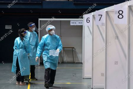 Medical professionals collect nasal swab sample at a makeshift testing site in the Queen Elizabeth Stadium in Hong Kong . Hong Kong began a voluntary mass-testing program for coronavirus Tuesday as part of a strategy to break the chain of transmission in the city's third outbreak of the disease