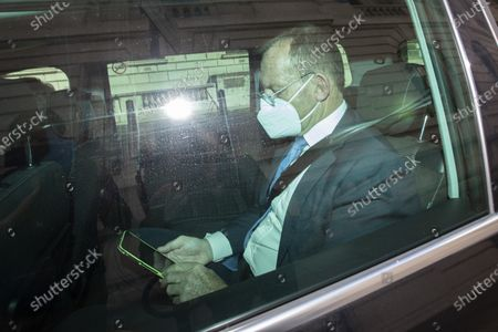Former Australian Prime Minister Tony Abbott wears a mask as he is driven away from 8 Great George Street after speaking at a Policy Exchange event.