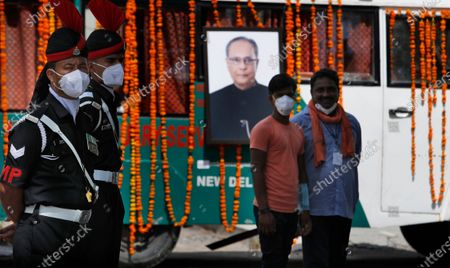 Indian Army soldiers stand during the cremation of former Indian President Pranab Mukherjee, seen in photograph, in New Delhi, India, . Mukherjee, a senior leader of India's Congress party who served in multiple Cabinets during five decades in politics, died on Monday. He was 84