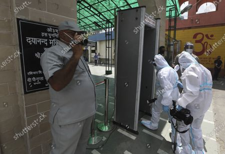 Official media personnel wearing personal protective suits arrive for the cremation of former Indian President Pranab Mukherjee in New Delhi, India, . Mukherjee, a senior leader of India's Congress party who served in multiple Cabinets during five decades in politics, died on Monday. He was 84