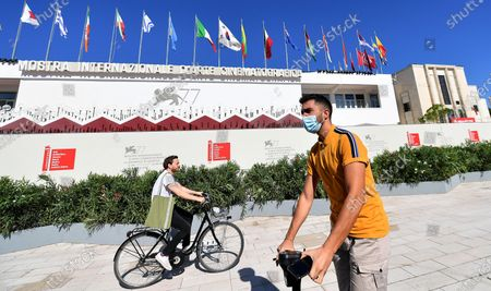 People pass by the festival palace ahead of the 77th annual Venice International Film Festival, in Venice, Italy, 01 September 2020. The movie 'Lacci' (The Ties) by Italian director Daniele Luchetti will open the film festival that runs from 02 to 12 September 2020.