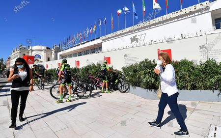 People wearing protective face masks walk in front of the festival palace ahead of the 77th annual Venice International Film Festival, in Venice, Italy, 01 September 2020. The movie 'Lacci' (The Ties) by Italian director Daniele Luchetti will open the film festival that runs from 02 to 12 September 2020.