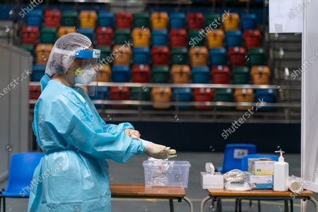A medical profession puts on a pair of gloves at a makeshift testing site in the Queen Elizabeth Stadium in Hong Kong, China, 01 September 2020. A Covid-19 testing programme begins at 141 sample collection centres across all 18 districts in city.
