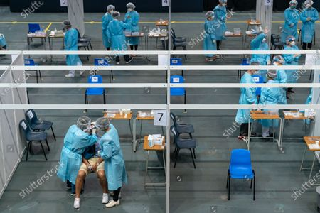 Medical professionals collect samples from a man at a makeshift Covid-19 testing site at the Queen Elizabeth Stadium in Hong Kong, China, 01 September 2020. A Covid-19 testing programme begins at 141 sample collection centres across all 18 districts in city.