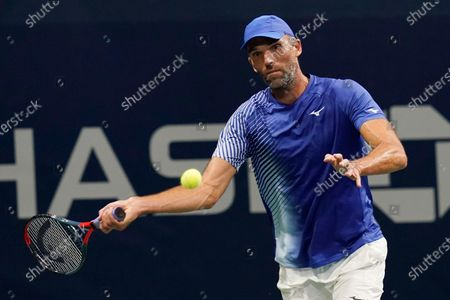 Stock Image of Ivo Karlovic, of Croatia, returns a shot to Richard Gasquet, of France, during the first round of the U.S. Open tennis championships, in New York