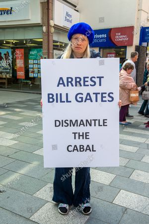 "A lady stands with an Arrest Bill Gates, Dismantle the Cabal banner in Maidenhead High Street. Her view is that the Coronavirus Pandemic was actually a ""Scamdemic"" that was planned by some people decades ago and is being financed by people such as Bill Gates as a smoke screen to ""bring in the new world order"""